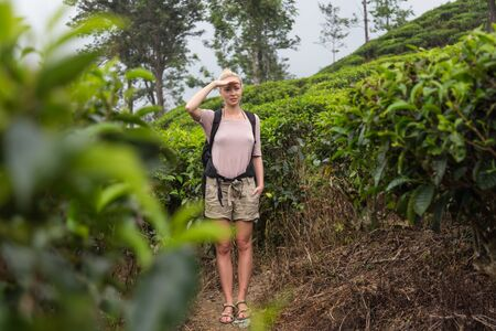 Active caucasian blonde woman enjoing fresh air and pristine nature while tracking among tea plantaitons near Ella, Sri Lanka. Bacpecking outdoors tourist adventure.