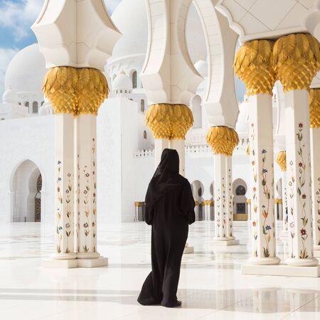 Traditionally dressed arabic woman wearing black burka wisiting Sheikh Zayed Grand Mosque in Abu Dhabi, United Arab Emirates.
