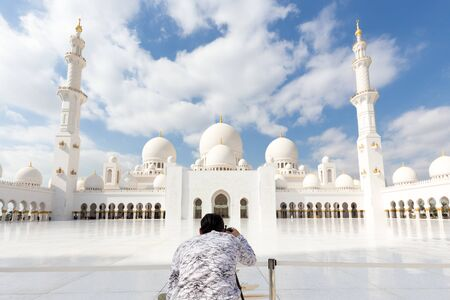 Male tourist taking photo of Sheikh Zayed Grand Mosquem main landmark in Abu Dhabi, the capital city of United Arab Emirates.