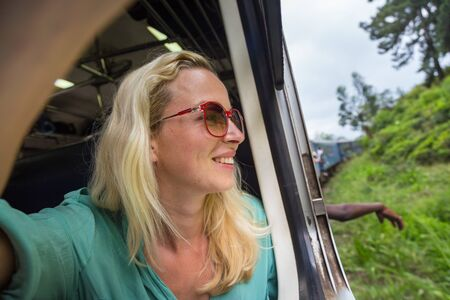 Happy smiling woman looks out from window traveling by train on most picturesque train road in Sri Lanka. 写真素材
