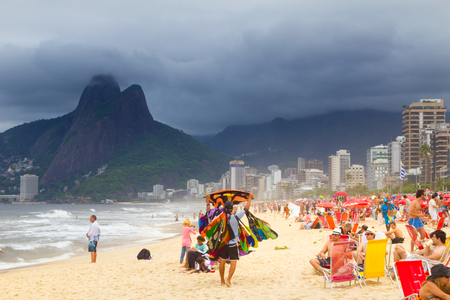 Rio de Janeiro, Brazil - Nov 03 2012: Tourist and local people peacefully enjoying on a lively Ipanema beach before the opcoming tropical storm on Copacabana, Rio de Janeiro, Brazil, on 3th of Novembe