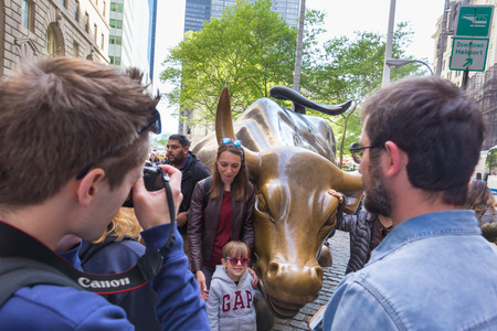 New York City, USA - May 18, 2018: Tourists taking photos of Charging Bull, landmark in Lower Manhattan representing the strength and power of the American People, on 18th of May, 2018 in NY, USA.