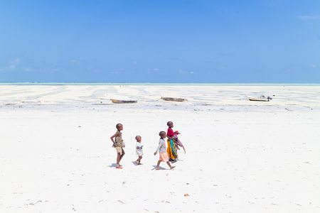 Paje, Zanzibar - Feb 9, 2015: Local kids walking at Paje village picture perfect white beach at low tide on February 9th, 2015 on Zanzibar, Tanzania.