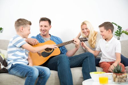 Happy caucasian family smiling while playing guitar and singing songs together at cosy modern home. Spending quality leisure time with children and family concept.