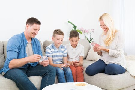 Happy young family playing card game on living room sofa at home. Spending quality leisure time with children and family concept.