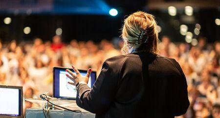 Vrouwelijke spreker die een bespreking op collectieve bedrijfsconferentie geeft. Onherkenbare mensen in het publiek in de conferentiezaal. Bedrijfs- en ondernemerschapsevenement.