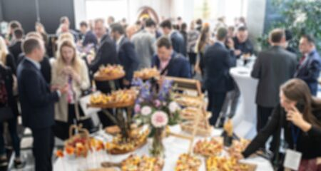 Abstract blurred photo of business people socializing during banquet lunch break break at business meeting, conference or event. Stock Photo
