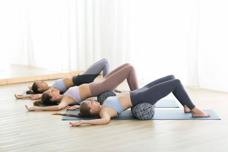 Restorative yoga with a bolster. Group of three young sporty attractive women in yoga studio, lying on bolster cushion, stretching and relaxing during restorative yoga. Healthy active lifestyle. 版權商用圖片