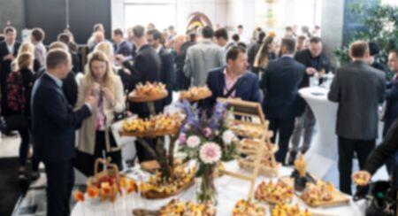 Foto borroneada abstracta de gente de negocios socializando durante la pausa del almuerzo del banquete en la reunión de negocios, conferencia o evento. Empresa y Emprendimiento. Foto de archivo