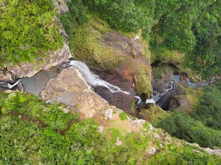 Aerial top view of travel couple waving to drone, standing on the edge of 500 feet waterfall in the tropical island jungle of Black river gorges national park on Mauritius island.