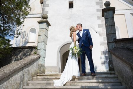 The Kiss. Bride and groom kisses tenderly on a staircase in front of a small local church. Stylish wedding couple kissing.