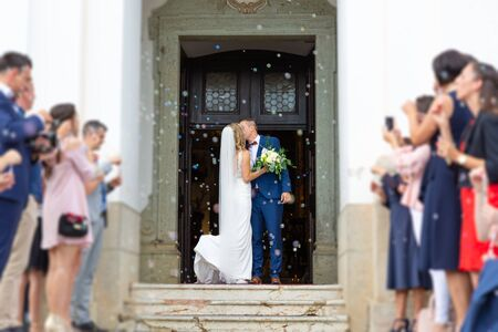 Newlyweds kissing while exiting the church after wedding ceremony, family and friends celebrating their love with the shower of soap bubbles, custom undermining traditional rice bath.