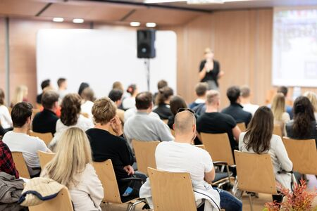 Business and entrepreneurship symposium. Female speaker giving a talk at business meeting. Audience in conference hall. Rear view of unrecognized participant in audience. Stockfoto