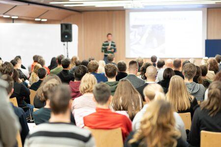 Conférencier donnant une présentation dans une salle de conférence à l'université. Les participants écoutent la conférence et prennent des notes.