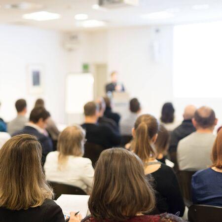 Spreker houdt een lezing in conferentiezaal op zakelijke evenement. Publiek in de conferentiezaal. Bedrijfs- en ondernemerschap concept. Focus op onherkenbare mensen in het publiek. Stockfoto