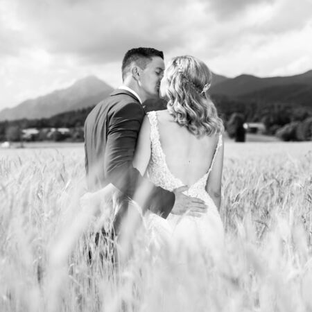 Bride and groom kissing and hugging tenderly in wheat field somewhere in countryside in Slovenia. Caucasian happy romantic young couple celebrating their marriage. Black and white photo. Foto de archivo