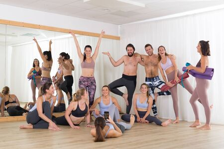 Group of young authentic real sporty attractive people in yoga studio having fun relaxing and socializing after hot yoga class. Healthy active lifestyle, working out in gym.