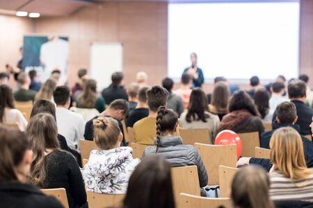 Sprecher, der Präsentation im Hörsaal der Universität hält. Die Teilnehmer hören dem Vortrag zu und machen sich Notizen.
