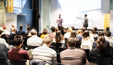 Relatore che tiene un discorso nella sala conferenze durante un evento aziendale. Pubblico presso la sala conferenze. Concetto di impresa e imprenditorialità. Concentrati sulle persone irriconoscibili nel pubblico.