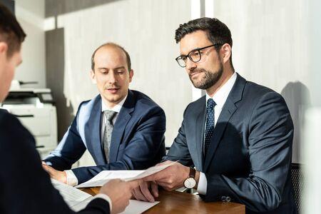 Équipe d'hommes d'affaires confiants et prospères examinant et signant un contrat pour sceller l'accord lors d'une réunion d'affaires dans un siège social moderne. Concept d'entreprise et d'entrepreneuriat. Banque d'images