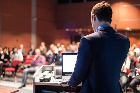 Prelegent wygłaszający prelekcję na korporacyjnej konferencji biznesowej. Nie do poznania ludzie na widowni w sali konferencyjnej. Wydarzenie Biznes i Przedsiębiorczość.