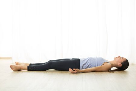 Portrait of gorgeous active sporty young woman practicing yoga in studio. Beautiful girl relaxing in Savasana, corpse pose. Healthy active lifestyle, working out indoors in gym. Banque d'images