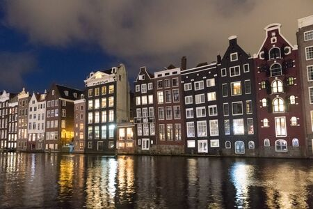Amstedam, capital of Netherlands. Beautiful tranquil scene of city of Amsterdam at dusk. Bicycles along the street and on the bridge over the canal.