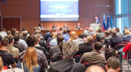Business and entrepreneurship symposium. Speaker giving a talk at business meeting. Audience in conference hall. Rear view of unrecognized participant in audience. Archivio Fotografico