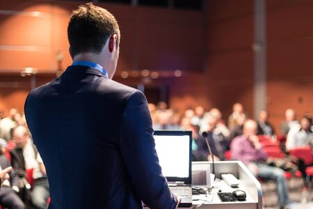 Speaker giving a talk on corporate business conference. Unrecognizable people in audience at conference hall. Business and Entrepreneurship event. Stockfoto