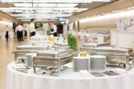 Waiters prepare buffet before a coffee break at business conference meeting. Stock Photo