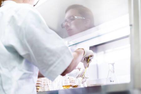 Female scientist working with laminar flow at coronavirus vaccine development laboratory research facility.