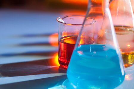 Illuminated laboratory flask filed with colorful chemical solutions with shadows on the table. Laboratory, science, reaserch, chemistry... consept.