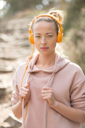 Portrait of beautiful sports woman with hoodie and headphones during outdoors training session. Healthy lifestyle image of young caucasian woman jogging outside.