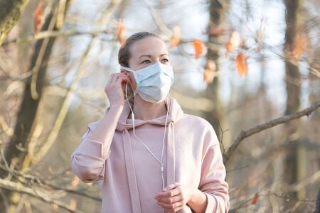 Portrait of caucasian sporty woman wearing medical protection face mask while walking in park, relaxing and listening to music. Corona virus, or Covid-19, is spreading all over the world. Stock Photo