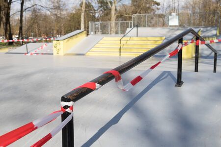 Corona virus COVID-19 restriction. No people due to quarantine. Closed urban skate park. Empty park and playground. Stay at home compaign. Red warning tape on ramps and slides. Social distancing.