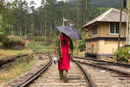 Woman wearing traditional sari and black umbrella walking home from her work on railway tracks in Sri Lanka.