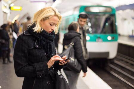 Młoda kobieta w płaszczu zimowym z telefonem komórkowym w dłoni czeka na peronie dworca kolejowego na przyjazd pociągu. Transport publiczny.