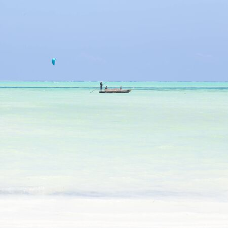 Solitary fishing boat and a kite surfer on picture perfect white sandy beach with turquoise blue sea, Paje, Zanzibar, Tanzania. Copy space. Imagens