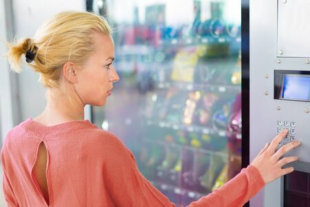 Caucasian woman using a modern vending machine. Her right hand is placed on the dia pad.