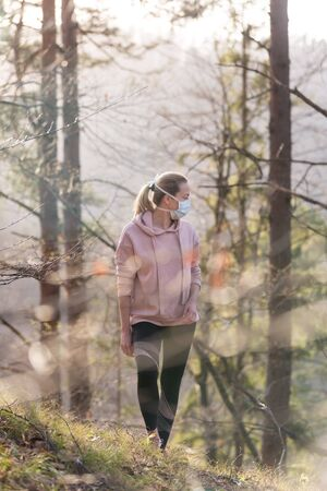 Portrait of caucasian sporty woman wearing a medical protection face mask while walking in the forest. Corona virus, or Covid-19, is spreading all over the world.