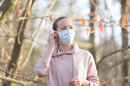 Portrait of caucasian sporty woman wearing medical protection face mask while walking in park Banque d'images