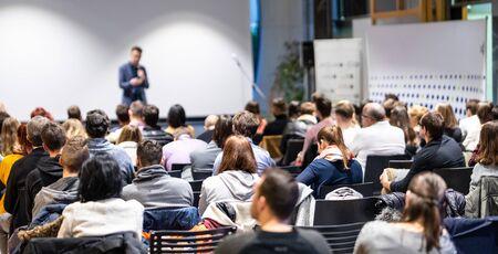 Conférencier donnant une conférence dans la salle de conférence lors d'un événement commercial. Vue arrière de personnes méconnaissables dans l'auditoire de la salle de conférence. Concept d'entreprise et d'entrepreneuriat. Banque d'images