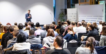 Speaker giving a talk in conference hall at business event. Rear view of unrecognizable people in audience at the conference hall. Business and entrepreneurship concept. Stockfoto