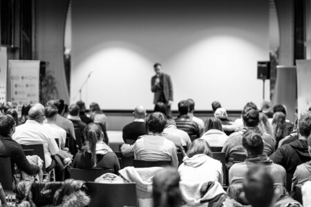 Speaker giving a talk in conference hall at business event. Audience at the conference hall. Business and Entrepreneurship concept. Focus on unrecognizable people in audience. Black and white image.