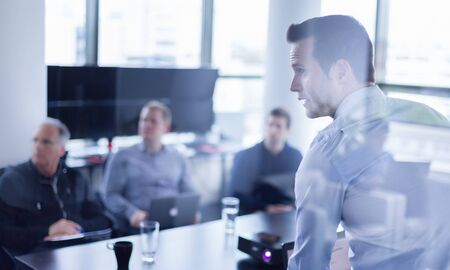 Biznesmen dokonywania prezentacji w biurze. Dyrektor biznesowy przedstawia prezentację swoim kolegom podczas spotkania lub wewnętrznego szkolenia biznesowego, wyjaśniając swoim pracownikom plany biznesowe.