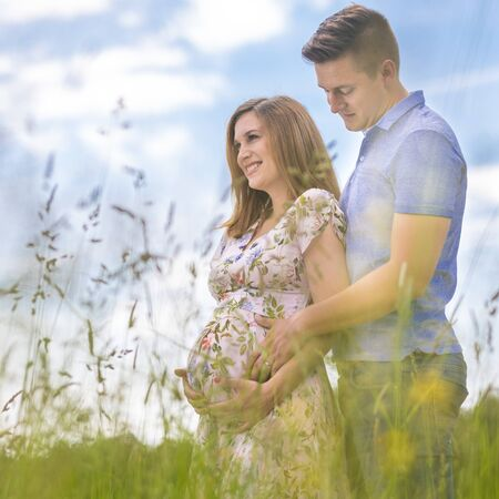 Young happy pregnant couple hugging in nature. Concept of love, relationship, care, marriage, family creation, pregnancy and parenting.