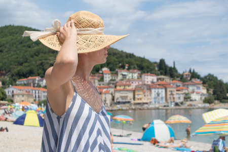 Lady wearing striped summer dress and straw hat relaxing on vaction enjoying view over beach at Moscenicka Draga, Istria, Croatia. Reklamní fotografie