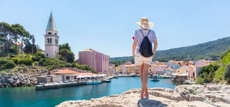 Woman traveler wearing straw summer hat and backpack, standing at edge of the rocky cliff enjoying beautiful panoramic view of Veli Losinj, Losinj island, Croatia. Zdjęcie Seryjne