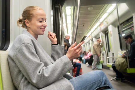 Portrait of lovely girl typing message on mobile phone in almost empty public subway train. Staying at home and social distancing recomented due to corona virus pandemic outbreak. Banco de Imagens