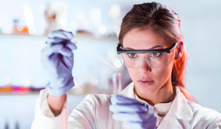 Life scientists researching in laboratory. Focused female life science professional pipetting solution into the glass cuvette. Lens focus on researchers eyes. Healthcare and biotechnology concept. Foto de archivo